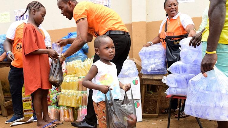 Ett föräldralöst barn i Freetown i Sierra Leone går med en plastpåse med mat som delats ut av frivilliga.