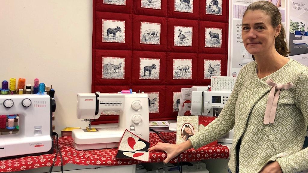 Ulrika Sandahl, som driver en symaskinsbutik, står framför flera symaskiner inne i butiken