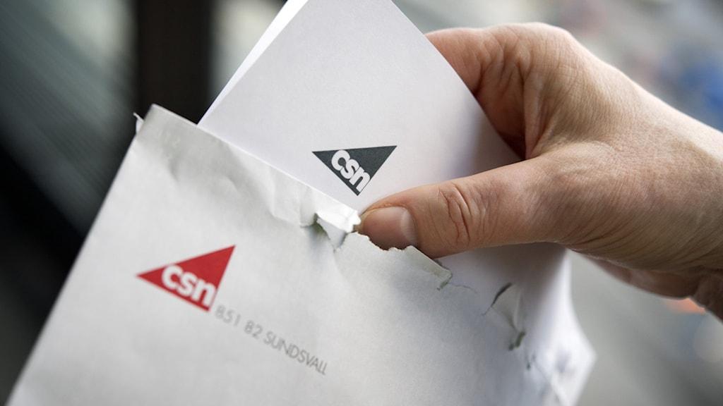 Person håller i kuvert märkta CSN.