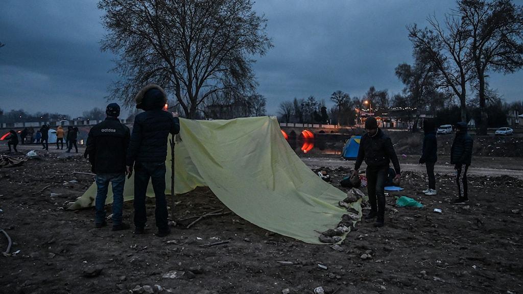 Tre personers ryggtavla och ett tält.