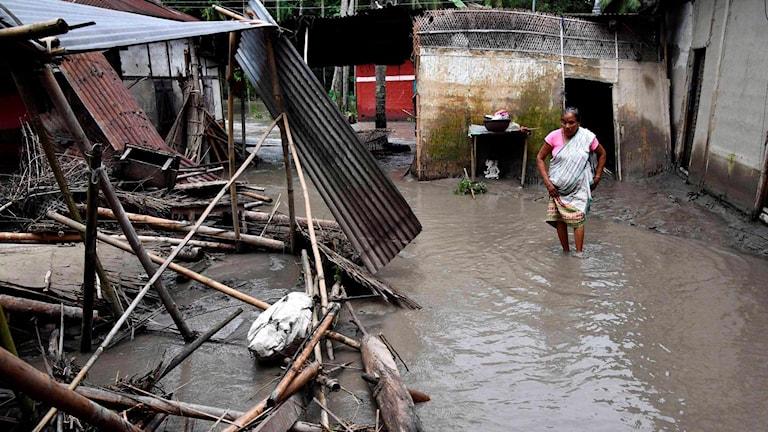 Kvinna som vadar i vatten bredvid ett raserat hus.