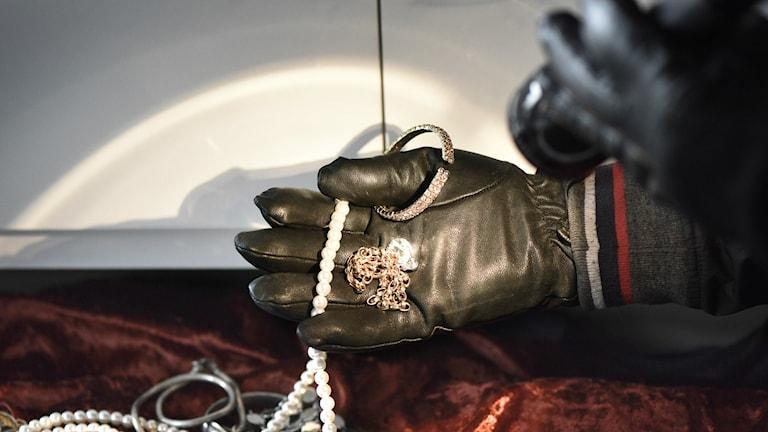 Bilden visar en handsklädd hand som tar upp smycken. Med den andra handen lyses med en ficklampa. Foto: Anders Wiklund/TT.