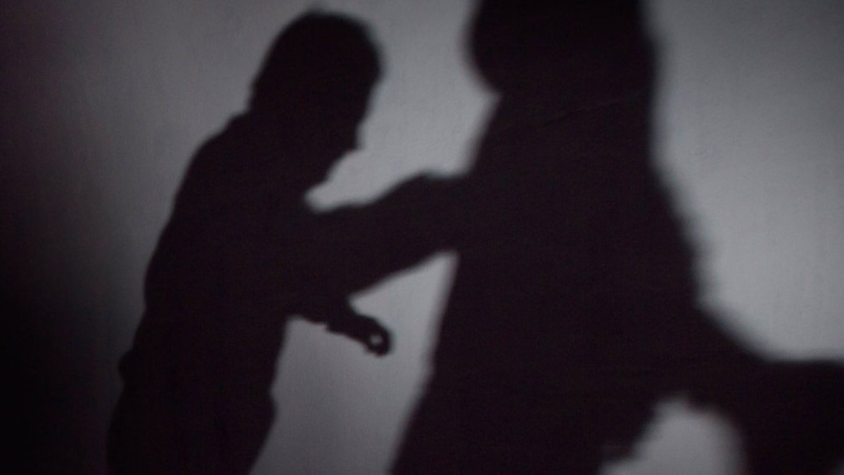 Två skuggfigurer i fingerad bild av våld.