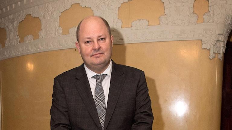 Thomas Mattsson står med händerna ihop mot en beige, lyxig vägg och ler.