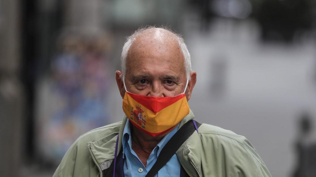 Man med munskydd föreställandes spanska flaggan. Madrid, Spanien.