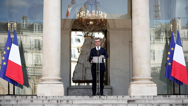 Man står vid podium mellan franska- och europeiska flaggan.