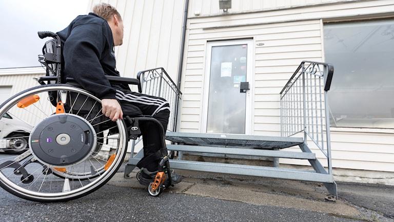Man i rullstol som inte kan komma upp för en trapp till en butik.
