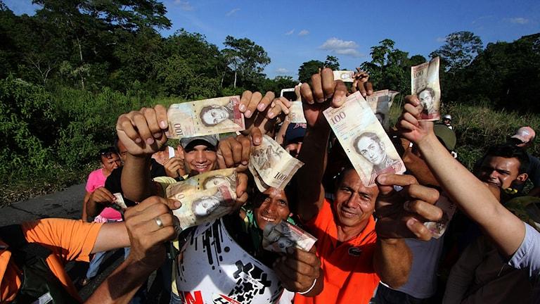 Folk håller upp den 100-Bolivar sedeln under protesterna i Venezuela