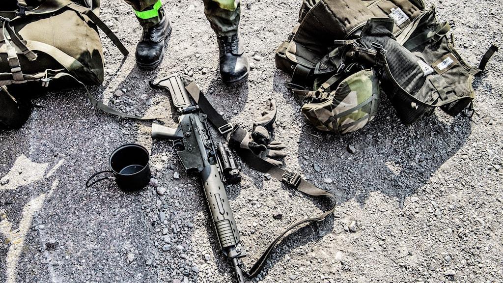 Skorna hos en soldat med vapen och annan utrustning spridd på marken.