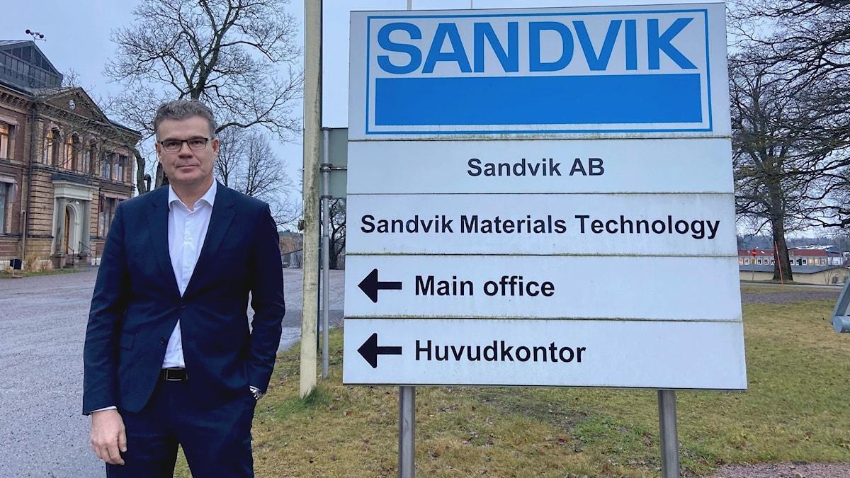 En kostymklädd man står bredvid en skylt där det både står bland annat Sandvik och Sandvik Materials Technology samt huvudkontor. I bakgrunden syns det gamla huvudkontoret, en tegelbyggnad.