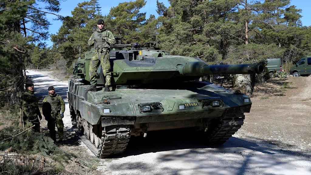 Stridsvagn och kamoulageklädda militärer.
