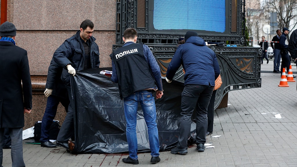 Poliser håller upp plast framför en kropp
