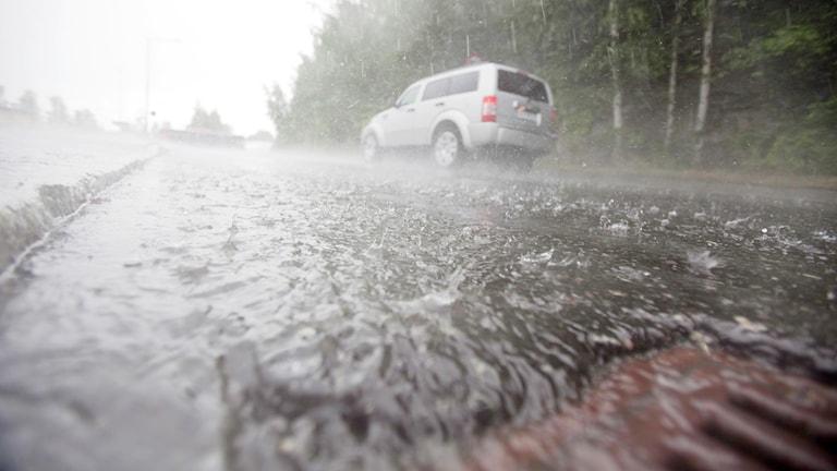 Regnoväder på väg. Vatten rinner ned i gatubrunn (arkivbild).