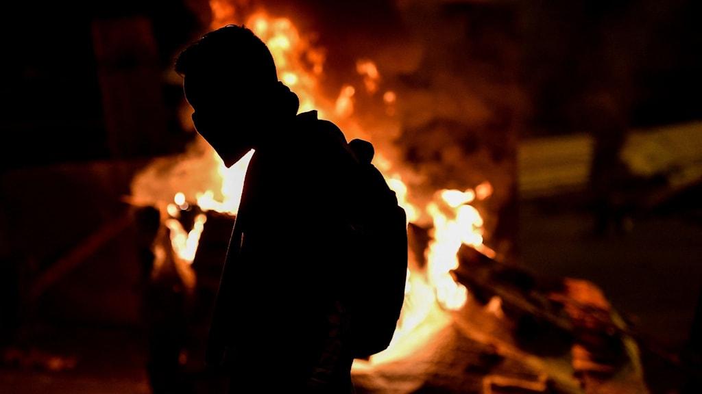 en demonstrant framför en eld.