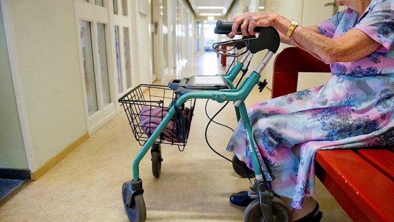 En äldre kvinna med rollator sitter på en bänk i en korridor