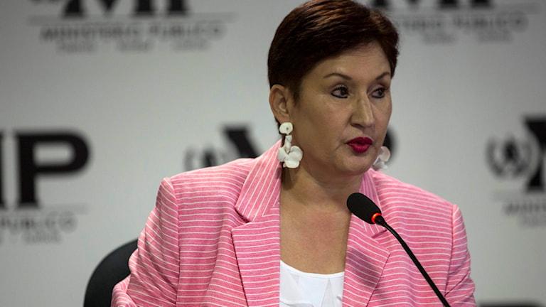 Thelma Aldana i rosa kavaj stående vid en mikrofon.