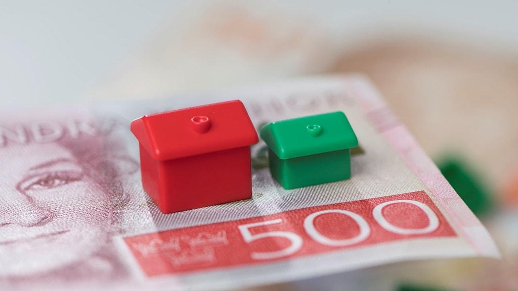 Två små Monopolhus som står på en 500-lapp.