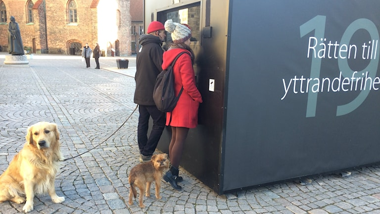 Bilden visar två personer som tittar på en film om yttrandefrihet som visas i en kub, som ställts upp på Domkyrkoplatsen i Lund. Två hundar väntar. Foto: Anna Bubenko/Sveriges Radio.