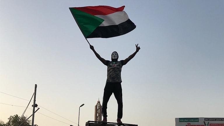 Man med Guy Fawkes-mask viftar med Sudans flagga.