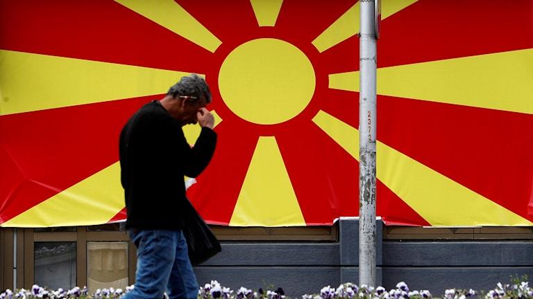man går framför nordmakedoniens flagga