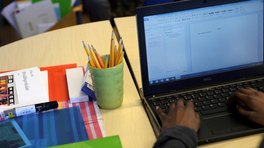 Skolbänk med pojke som sitter vid en laptop.