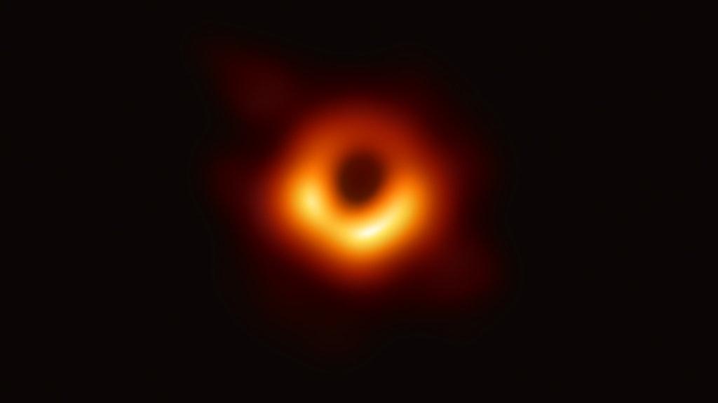 Ljusröd cirkel mot svart yta är en bild av ett svarta hål i rymden.