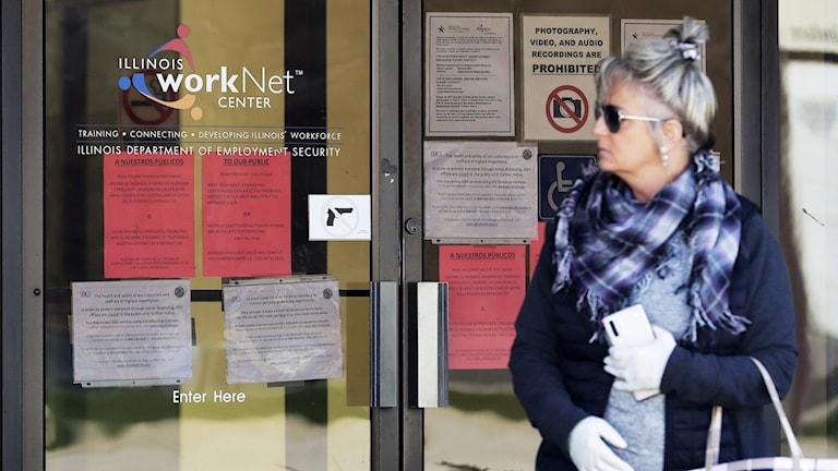 Kvinna tittar på jobbannonser utanför ett myndighetskontor i USA.