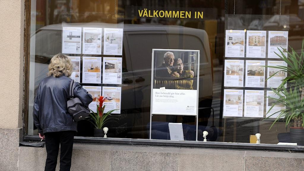 En kvinna tittar på bostadsannonser i ett skyltfönster utanför en mäklarfirma