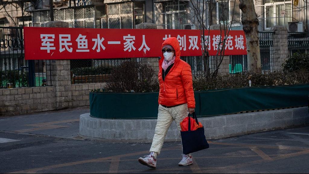 Kvinna i Kina bär en skyddsmask för att undvika att smittas av det nya coronaviruset.
