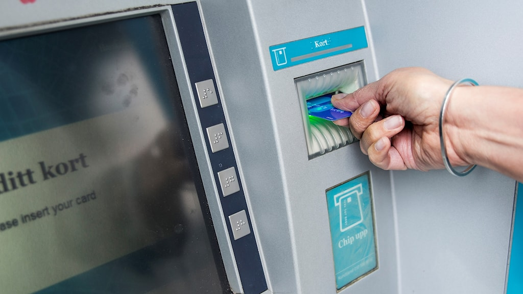 Kvinna tar ut pengar ur bankomat