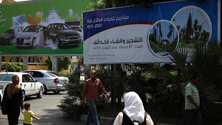 Gående framför valskylt i Gaza City.