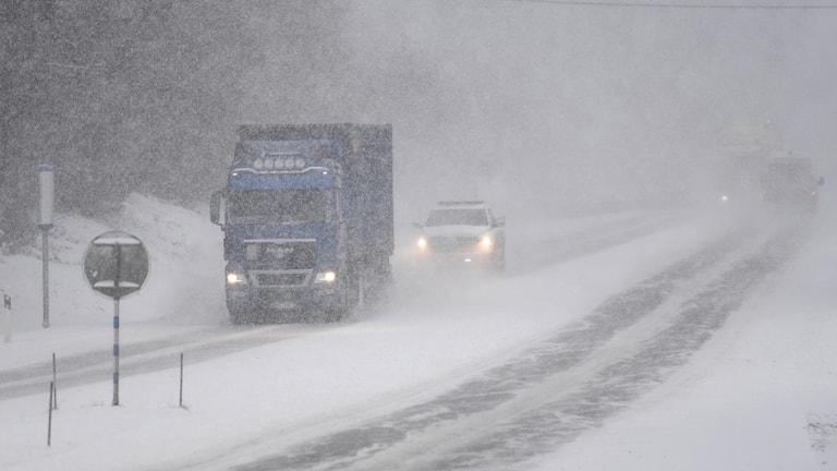 En lastbil och en bil kör på en väg medan snö faller.