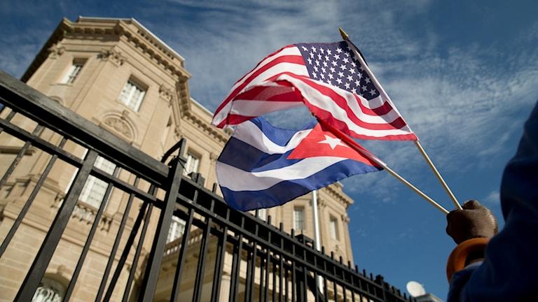 En person håller upp en amerikansk och en kubansk flagga framför ett staket och ett hus.