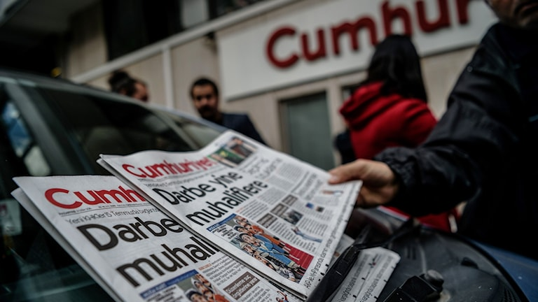 En man tar en turkisk tidning
