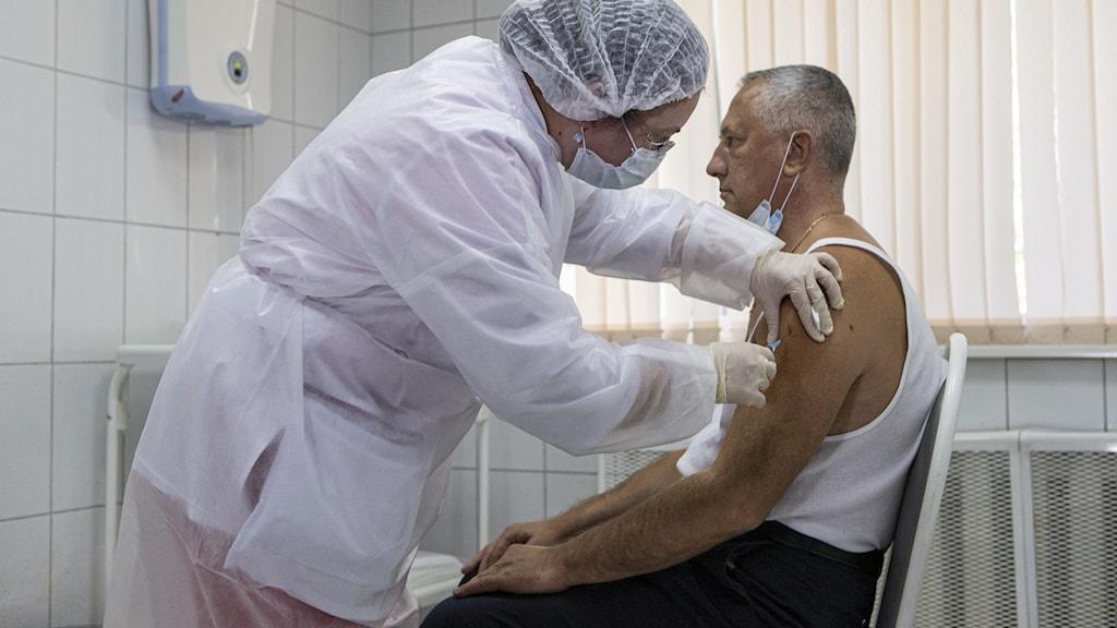 En man vaccineras med coronavaccinet Sputnik V.
