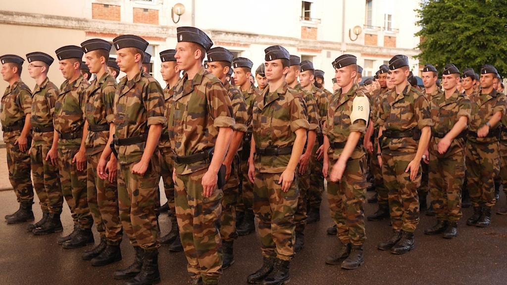 Tredje plutonen på Gendarmerie-skolan i Montluçon står uppställda i militäruniformer.