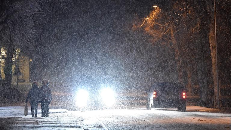 Två personer går på en väg, det snöar mycket och det är mörkt, mot dem kommer en bil