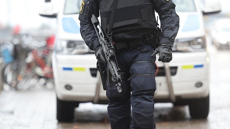 En polis och en polisbil.