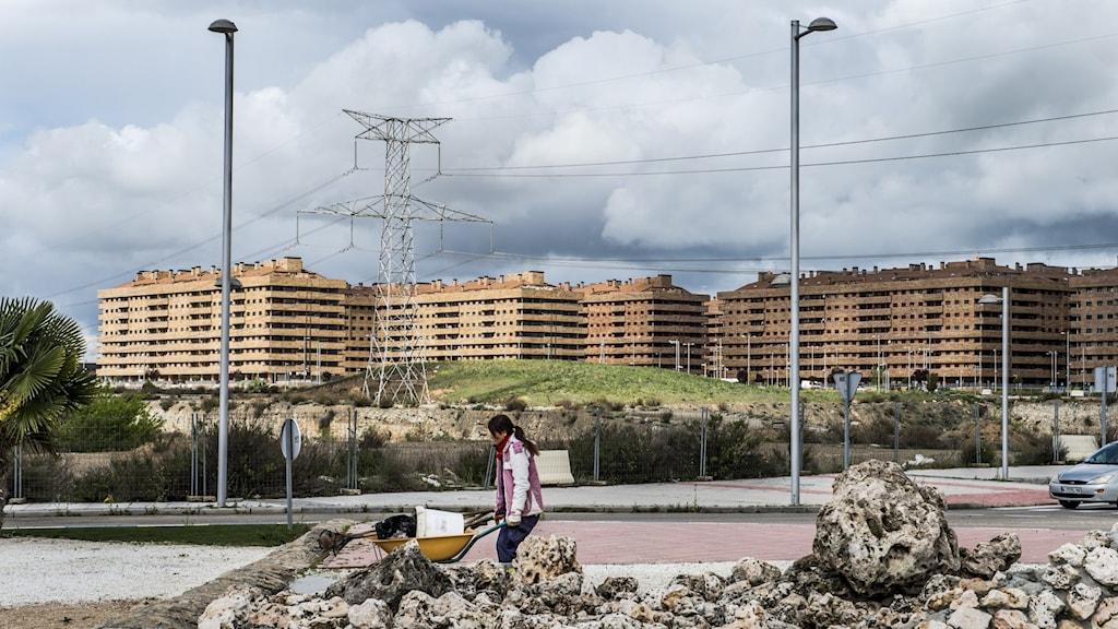 person kör grävskopa framför bostadskomplex och elledningar.