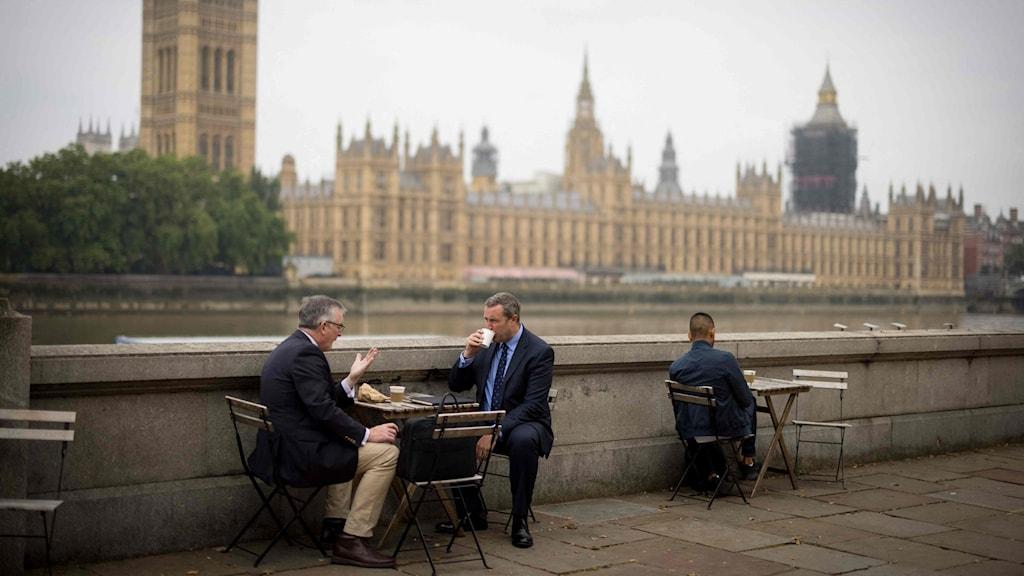 Två män fikar vid Themsen i London