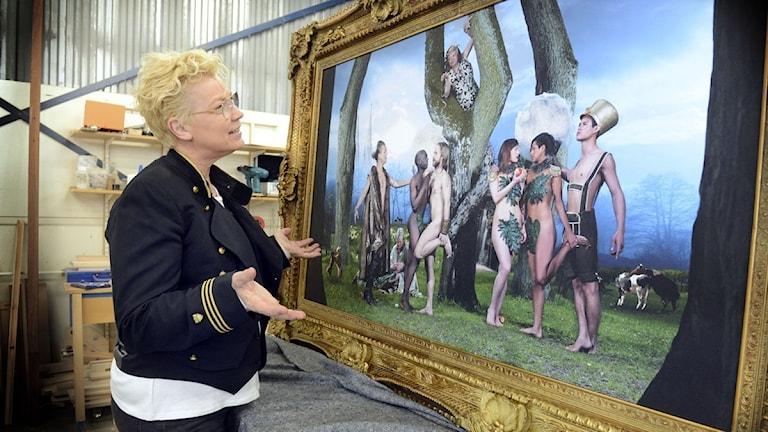 En kvinna står vänd mot en tavla med öppna armar