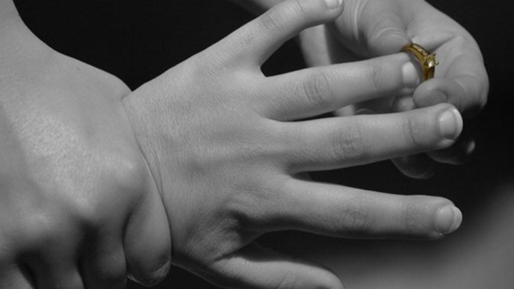 Fasthållen hand med ring.