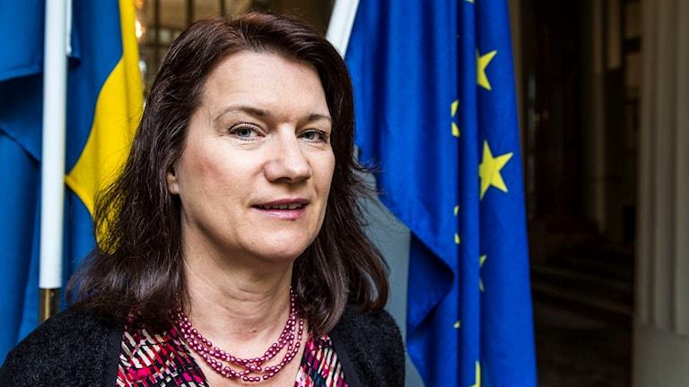 Ann Linde med en EU-flagga i bakgrunden