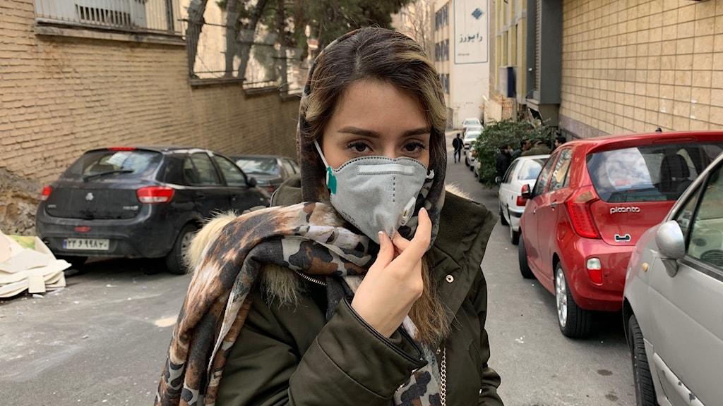 Kvinna med munskydd på en gata.