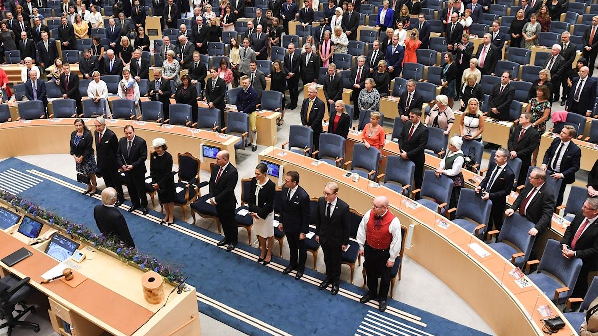 Riksdagsledamoterna och kungafamiljen ställer upp sig i plenisalen i riksdagshuset inför riksmötets öppnande. Foto: Fredrik Sandberg / TT