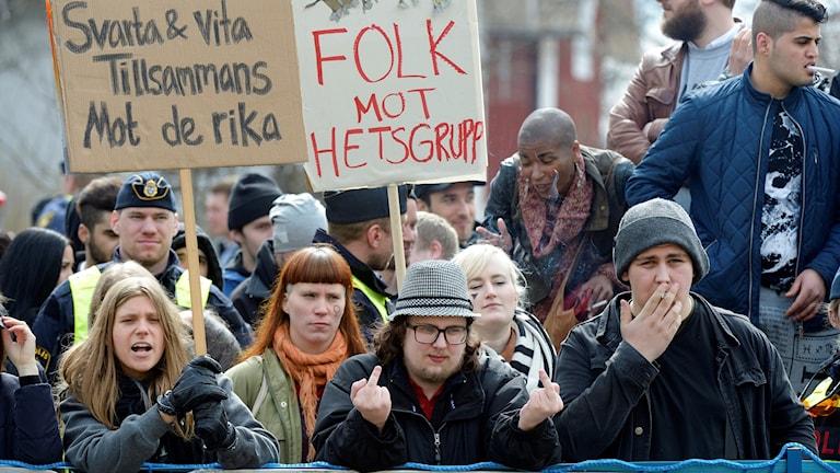 Man med hatt sträcker upp två långfingrar framför en skylt med texten Folk mot hetsgrupp.