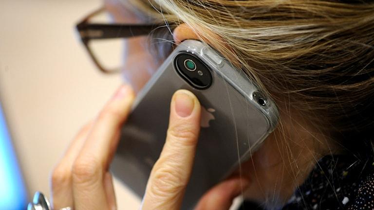 En kvinna pratar i en smartphone
