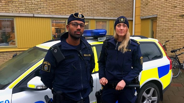 Mattias Andersson och Emma Jonasson framför en polisbil.