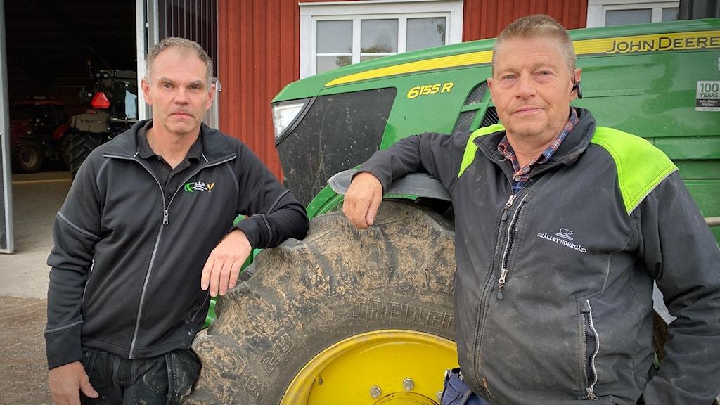 Två män står lutade mot en traktor.