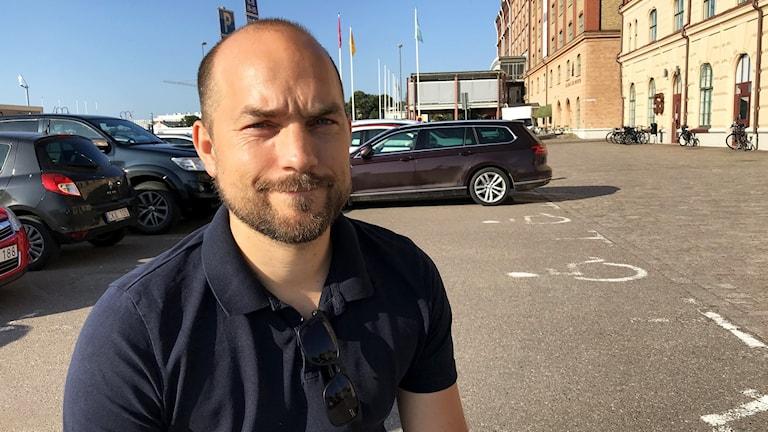 En man utomhus som tittar in i kameran.